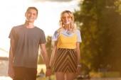 Fotografia giovani coppie che tengono le mani sulla spiaggia del fiume in serata e che guarda lobbiettivo sorridenti