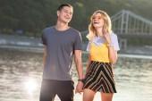 Fotografie směje se mladý pár, drželi se za ruce a chůzi na pláži řeka večer