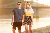 Fotografie young couple in sunglasses holding hands on river beach in evening