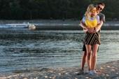 Fotografie boyfriend cuddling girlfriend on river beach
