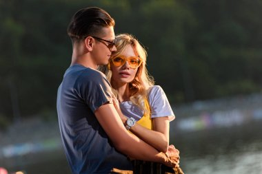 young couple hugging on river beach in evening, girlfriend looking at camera