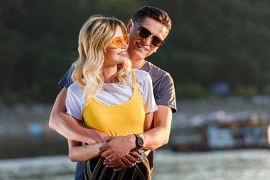smiling boyfriend cuddling girlfriend on river beach in evening