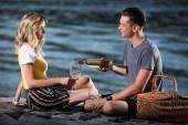 boční pohled na přítele, nalil víno v brýlích na pikniku na pláži řeka v večer