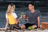 boční pohled na mladý pár, cinkání s pohárky na pikniku na pláži řeka večer