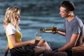 veselý přítel nalil víno v brýlích na pikniku na pláži řeka v večer