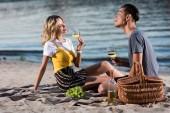 mladý pár se baví na pikniku na pláži řeka večer