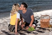 young couple kissing at picnic on river beach in evening