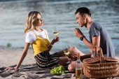young couple drinking wine and eating grapes at picnic on river beach in evening