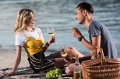 usmíval se mladý pár pil víno a jíst hrozny na pikniku na pláži řeka večer