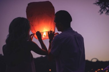 back view of young couple launching sky lantern on river beach in evening