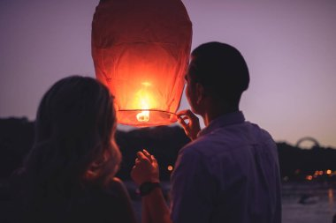 rear view of young couple launching sky lantern on river beach in evening