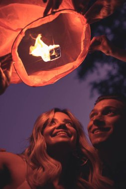 low angle view of smiling young couple launching sky lantern on river beach in evening
