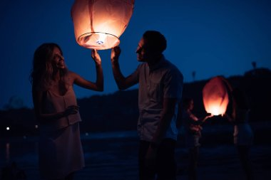 happy young couple launching sky lantern on river beach in evening