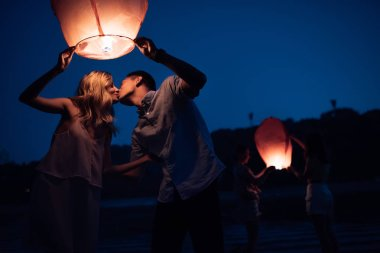 young couple kissing and launching sky lantern on river beach in evening