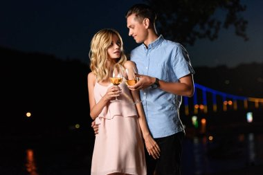 young couple clinking with glasses of wine and looking at each other on river beach in evening