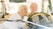 Zobrazit přes čelní sklo starší pár sedí v retro auta