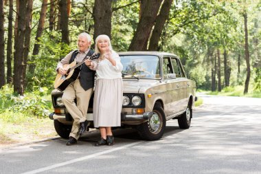 senior wife with husband playing guitar leaning on car on road in forest