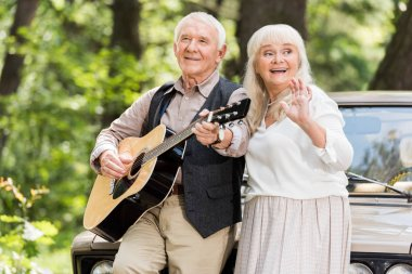 beautiful senior woman smiling with man playing guitar leaning on car