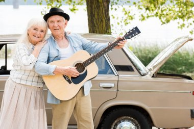 attractive senior woman embracing man playing guitar against beige vintage car
