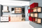 Photo interior of modern clean light kitchen with furniture and wooden red shelves