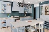 interiér moderní lehká kuchyně s bílým dřevěným nábytkem, stolem a židlemi