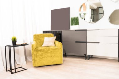 interior of bedroom with yellow armchair and mirrors