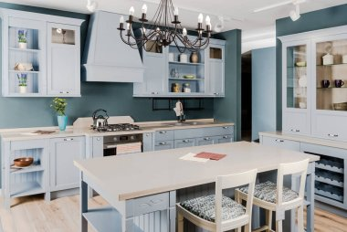 interior of modern light kitchen with white wooden furniture, table and chairs