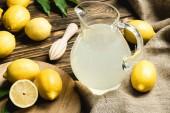 Skleněná konvice s čerstvým džusem, ždímací a žluté citrony na vyhození na dřevěný povrch