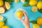 top view of female hand with lemons and squeezer on turquoise background