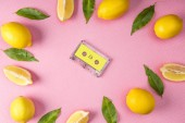 top view of frame made from yellow lemons and leaves with vintage audio cassette inside on pink