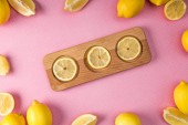 top view of fresh lemon slices on wooden board with lemons around on pink background