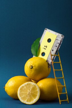 fresh lemons with vintage audio cassette and little ladder on blue