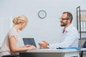 fyzioterapeut v bílém plášti s konverzaci s pacientka na pracovišti s notebookem v nemocnici