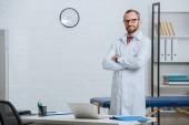 mužské chiropraktik v bílém plášti a brýle s rukama přes stojící na pracovišti s notebookem v nemocnici