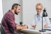 boční pohled na ženské chiropraktik ukázal na obrazovce přenosného počítače během schůzky s pacientem v nemocnici