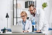 Fotografia fisioterapisti in camice bianco che utilizza computer portatile insieme nella clinica di sorridente
