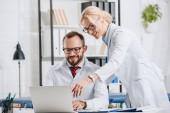 s úsměvem fyzioterapeutů v bílých pláštích společně pomocí přenosného počítače v klinice