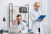 portrét fyzioterapeutů v bílých pláštích a brýle na pracovišti v klinice