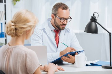 physiotherapist in white coat making notes in notepad with female patient near by during appointment in clinic