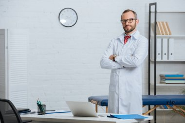 male chiropractor in white coat and eyeglasses with arms crossed standing at workplace with laptop in hospital