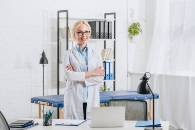 portrait of smiling chiropractor in eyeglasses and white coat standing at workplace in clinic