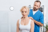 Fotografie portrét fyzioterapeut masíruje ramena Zenske v nemocnici