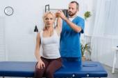 portrét chiropraktik táhnoucí Zenske rameno na masážní stůl v klinice