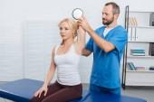 s úsměvem chiropraktik táhnoucí Zenske rameno na masážní stůl v klinice