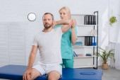 Fotografie portrait of physiotherapist stretching mans arm in hospital