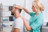 boční pohled na ženské masáž terapeut dělá masáž krku pacienta v klinice