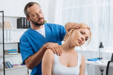 portrait of chiropractor stretching neck of woman during appointment in hospital