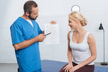 physiotherapist showing human body scheme to smiling woman on massage table in hospital