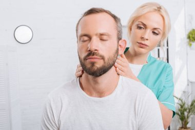 portrait of physiotherapist massaging man neck in clinic