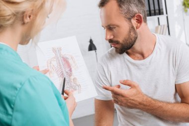 chiropractic showing human body picture to male patient during appointment in clinic